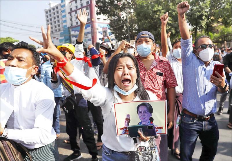 緬甸民眾十五日在仰光「全國民主聯盟」(NLD)中央黨部外集會,抗議軍方發動政變,一名女子手持翁山蘇姬的照片要求軍方立即釋放她。(歐新社)