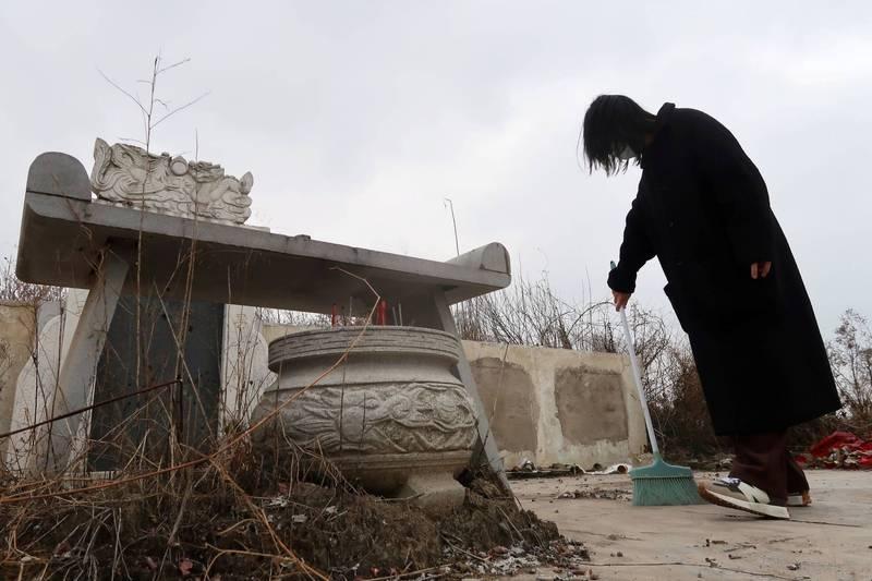 一名女子在武汉市的墓园祭悼因罹患武汉肺炎导致併发症而死的祖母和父亲。(路透档案照)(photo:LTN)