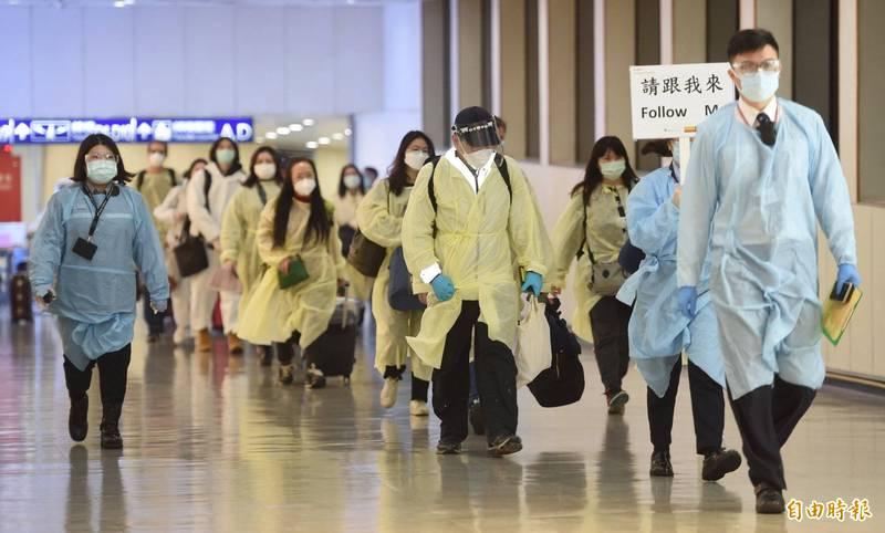 台灣防疫有成,受到德媒大讚。示意圖,圖為疾管署人員穿著防護衣引導旅客入境的畫面。(資料照)