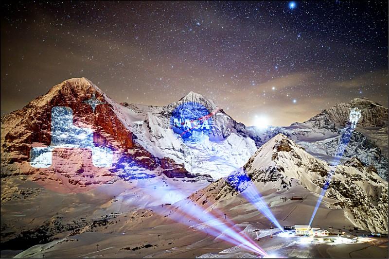 為了向美國航太總署(NASA)2020火星計畫致敬,瑞士燈光藝術家霍夫斯泰特(Gerry Hofstetter)14日在該國梅利菲(Mannlichen)高山度假勝地,藉由地面和直升機投影的方式,從左到右在艾格峰、僧侶峰與少女峰,分別打上NASA2020火星計畫的標誌、NASA的標誌及一名太空人的巨型圖案。(歐新社)