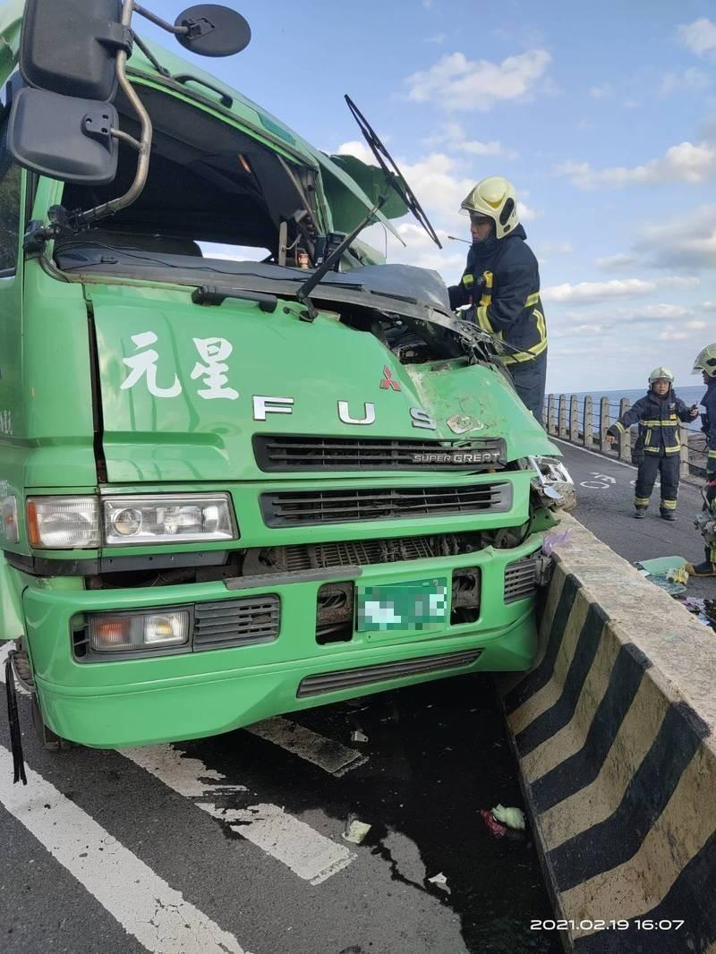 一輛貨櫃車今天下午行經台二線時,失控撞上分隔島後,後載貨櫃翻覆,駕駛受困變形的曳引車頭內;消防隊員將救出時已無意識,送醫急救中。(記者林嘉東翻攝)