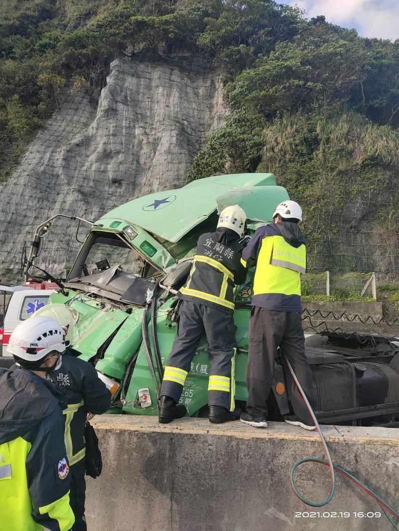 消防隊員救援受困車頭內的駕駛。(記者林嘉東翻攝)