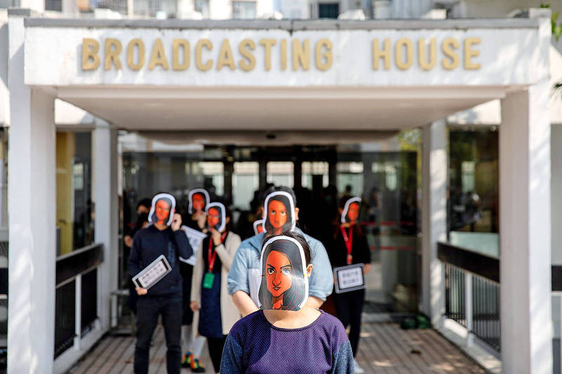 Radio Television Hong Kong journalists don masks representing their colleague Nabel Qoser, who had her civil service contract terminated after her tough questioning of government officials, during a protest outside their office in Hong Kong's Kowloon Tong on Jan. 28. Photo: EPA-EFE