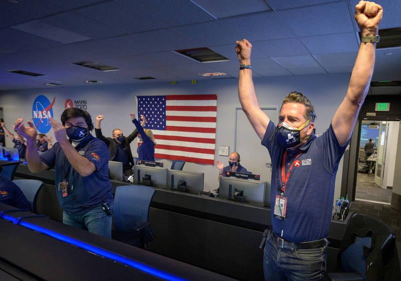 美國太空總署的火星的探測車「毅力號」今天順利登陸火星,監控中心的人員在確定毅力號順利著陸後紛紛拍手慶祝。(美聯社)