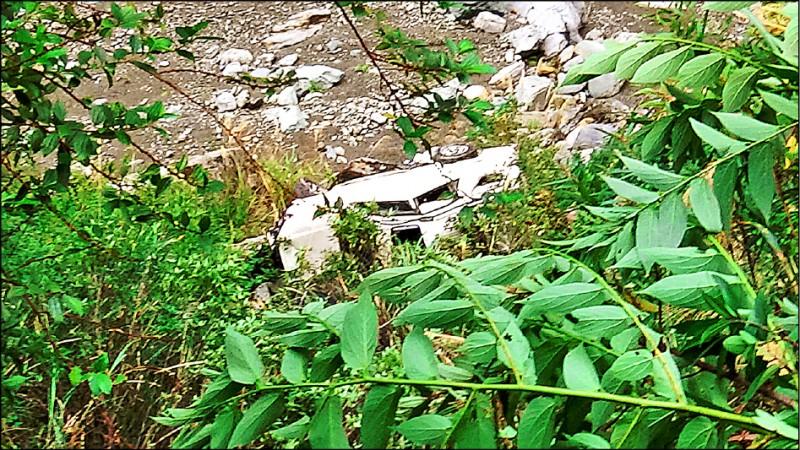 白色進口休旅車閃避落石,摔下15米深溪床人沒事!還能爬回林道。(警方提供)