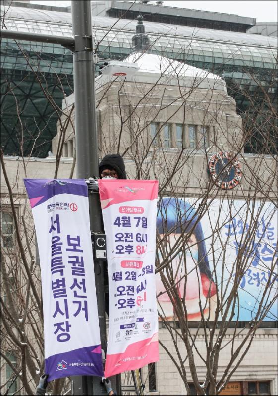 原首爾市長朴元淳於2020年7月9日自殺身亡,該職位預計4月7日補選。圖為一名工作人員2月在首爾市政府前,綑綁當局向市民宣傳補選投票及其日期、時間的布條。(歐新社)
