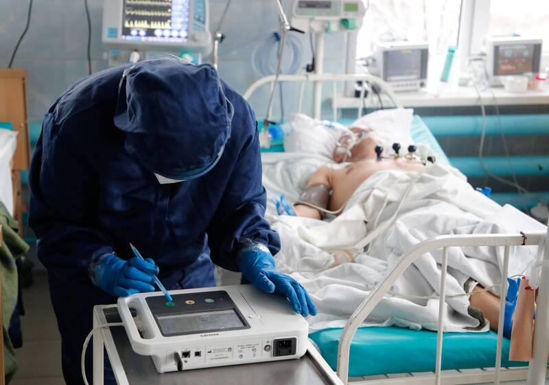 心臟雷達能幫助疫情期間的醫生,減少與病患接觸的機會,進而降低染疫風險。圖為穿戴全套防護裝備,替病患進行心電圖檢查的醫護人員。(路透檔案照)