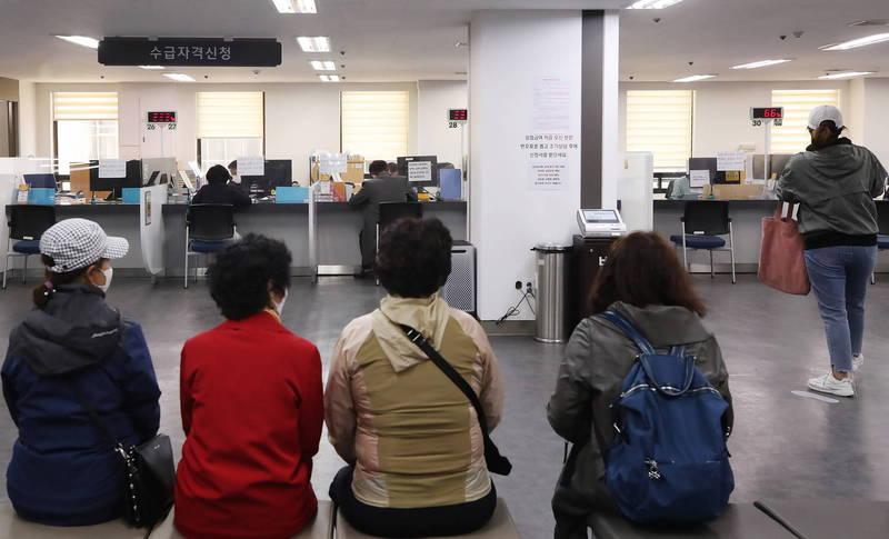 受疫情影響,南韓「放棄求職者」增多,女性占比創新高。圖為等待申請失業救濟金的南韓婦女。(歐新社)