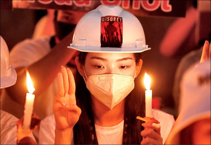緬甸民眾廿日點亮燭火、舉起象徵反抗極權的三指,為示威浪潮中首名死亡者苗兌兌凱(Mya Thwate Thwate Khaing)哀悼。(歐新社)