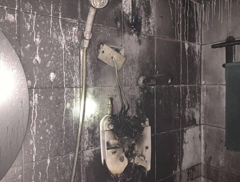 台中太平區中山路1段1棟大樓的出租套房,今晚1名男大生洗澡時電熱水器突然冒煙起火燒毀。(記者陳建志翻攝)