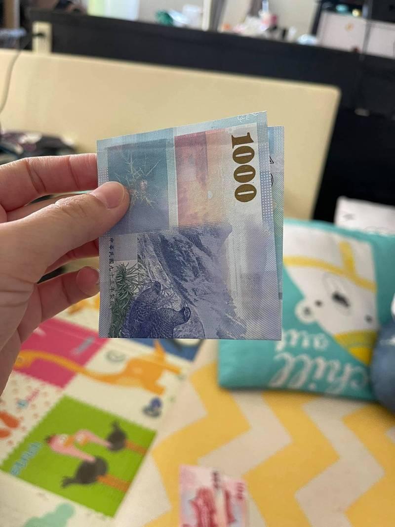 女網友打開時以為收到2張千元大鈔,一抽出來竟只是1張千元鈔。(圖擷取自臉書《爆廢1公社》)