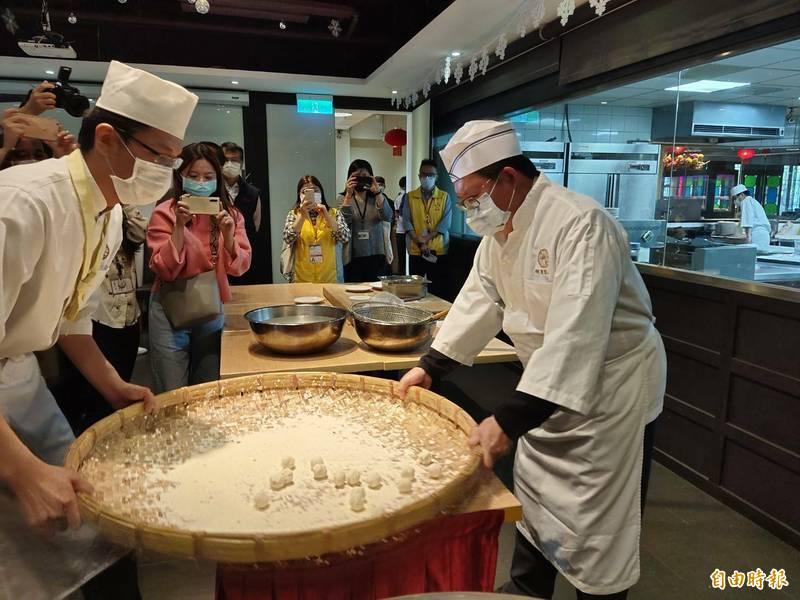 桃園市長鄭文燦參觀南僑食品工廠,和師傅手搖元宵。(記者謝武雄攝)