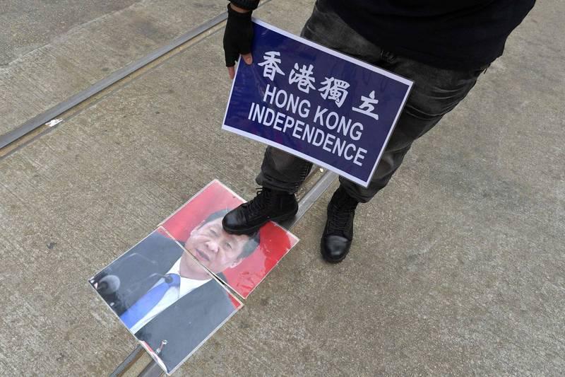 2019年9月香港反送中示威期間,示威者拿著「香港獨立」標語牌,踩在習近平的照片上。(法新社檔案照)