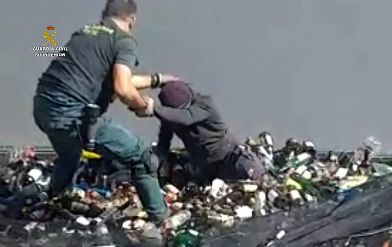 西班牙在北非領土麥里亞警方最近從港口裝滿廢棄玻璃罐等回收物的貨櫃中救出一群難民。(路透)