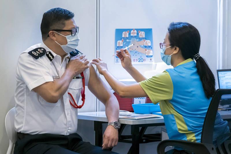 香港多個紀律部隊今天跟進施打科興疫苗,警務處處長鄧炳強接種後也呼籲所有香港市民登記。(彭博)