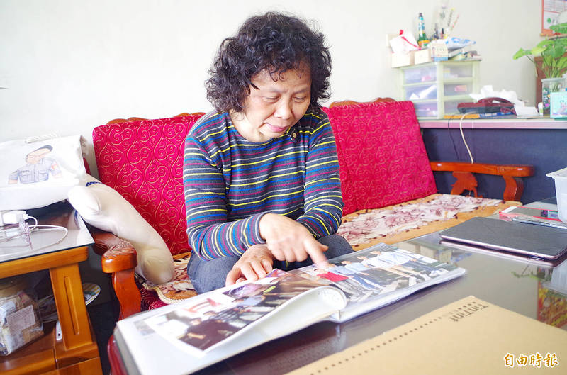 Chang Hsiu-chen, mother of murdered railway police officer Lee Cheng-han, points at a photo album in Chiayi yesterday after the High Court convicted her son's killer of homicide and sentenced him to 17 years in prison. Photo: Wang Shan-yen, Taipei Times