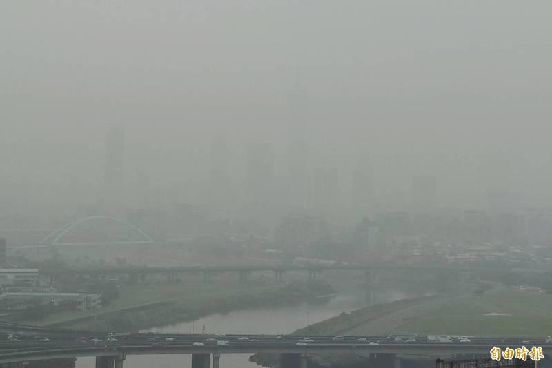 空氣品質不佳,環保署空氣品質監測顯示,今日(25日)西部各測站亮紅燈警示,台北101大樓下午快看不見了。(記者鹿俊為攝)