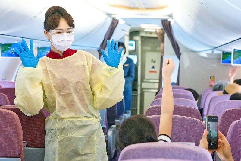 A China Airlines flight attendant wearing personal protective equipment talks with a passenger on Aug. 8 last year. Photo: CNA