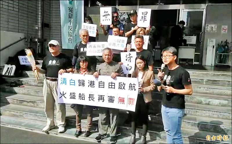 陳火盛(前排中)改判無罪,步出法院後與妻子(前排左二)舉無罪紙板。(記者鮑建信攝)