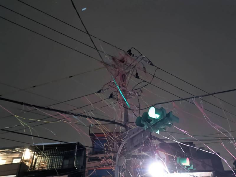 台北市社子島昨晚舉辦「夜弄土地公」元宵活動,大量的煙火彩帶纏繞電線桿,造成電線短路,意外引發停電災情。(讀者提供)