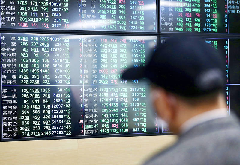A man looks at an electronic stock board at a brokerage firm in Taipei yesterday. Photo: CNA