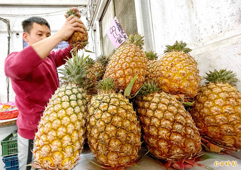 A man stacks pineapples at a market in Taipei yesterday. Photo: Liu Hsin-de, Taipei Times