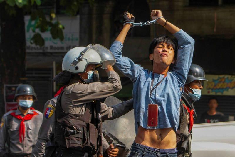 一名緬甸示威者在仰光遭到鎮暴警察逮捕,高舉被綁的雙手抗議。(路透)