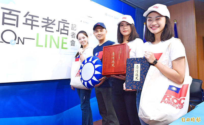 People hold Chinese Nationalist Party (KMT) merchandise and books about Taiwanese history at a news conference in Taipei to launch an online shopping portal on Nov. 17 last year. Photo: Liao Chen-huei, Taipei Times