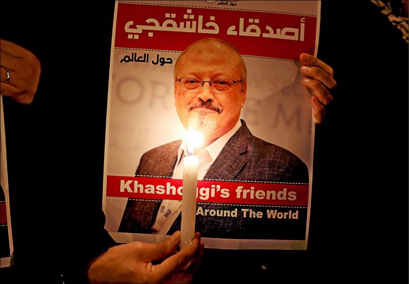 在華盛頓郵報記者哈紹吉遇害的沙國駐土耳其伊斯坦堡總領事館外,二○一八年十月示威者拿其肖像標語舉行燭光晚會。(路透檔案照)