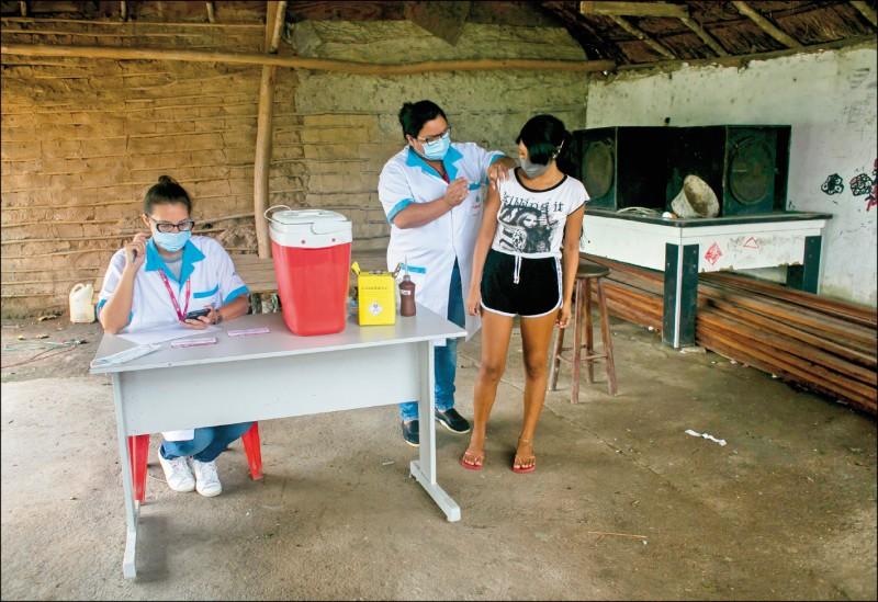 巴西展開大規模的接種計畫,圖為醫護人員在里約熱內盧一個村莊為婦女施打疫苗。(美聯社)
