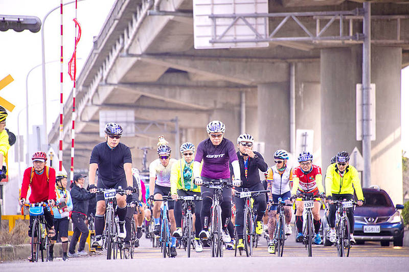 Taipei Mayor Ko Wen-je, front center, is accompanied by other cyclists yesterday on a ride along a Taipei road. Photo courtesy of Taipei City Government