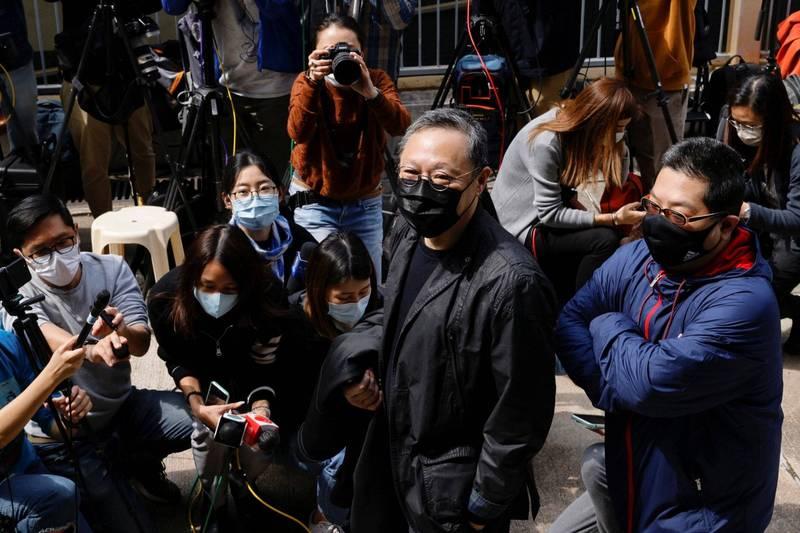 香港今年初被捕的50多名民主派人士,在陸續獲得保釋後今天(28日)突然被通知提前到警署報到,當中47人到場後被起訴「串謀顛覆國家政權罪」。圖為民主派港大法律系前副教授戴耀廷現身警局,立即被媒體包圍。(路透)
