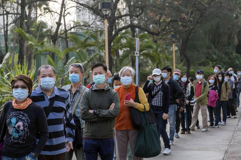 香港疫苗26日開打,昨有名72歲男子接種後感到心悸,緊急送醫。圖為排隊接種疫苗的民眾。(彭博社)