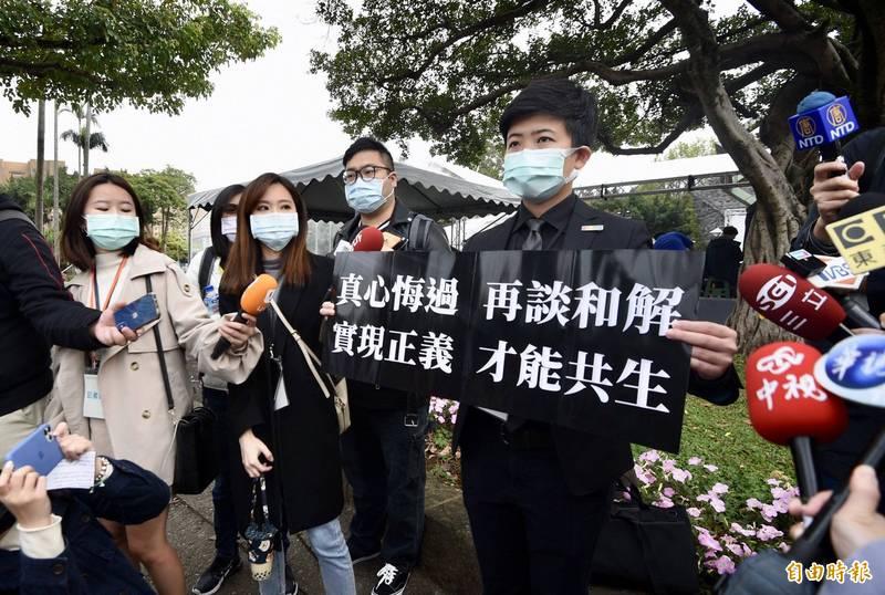 台北市政府28日於二二八公園舉辦「愛與勇氣 攜手同行」紀念會,台北市議員苗博雅在場舉「真心悔過 再談和解 實現正義 才能共生」標語,表達無聲抗議。(記者羅沛德攝)