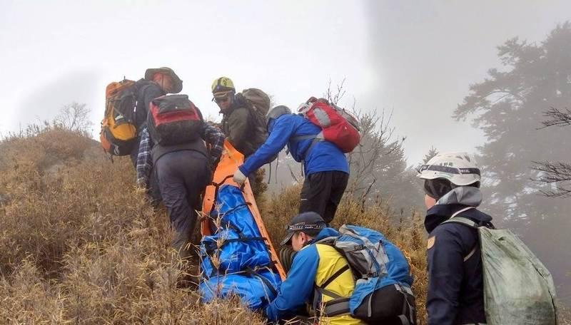 南投縣消防局搜救人員將在信義鄉郡大山墜崖罹難的女山友遺體搬運下山。(資料照,南投縣消防局提供)