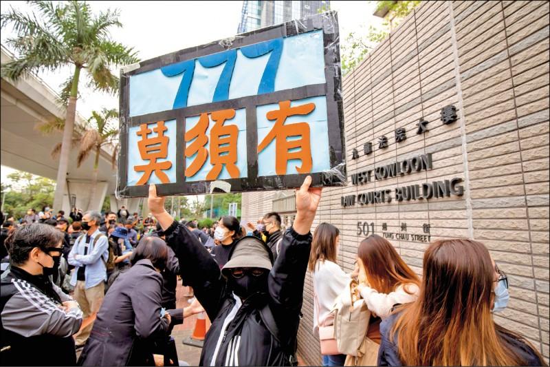 香港47名民主派人士被控串謀顛覆國家政權罪,昨日在西九龍裁判法院首次出庭。香港民眾身穿黑衣在法庭外聲援。(彭博)