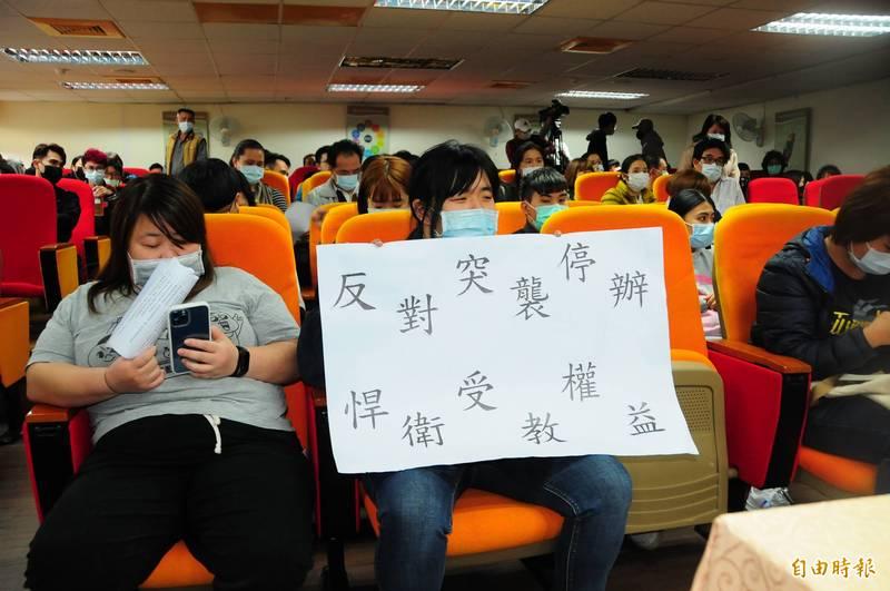 學生在教育部、學校說明會現場舉大字報「反對突襲停辦、捍衛受教權益」。(記者花孟璟攝)