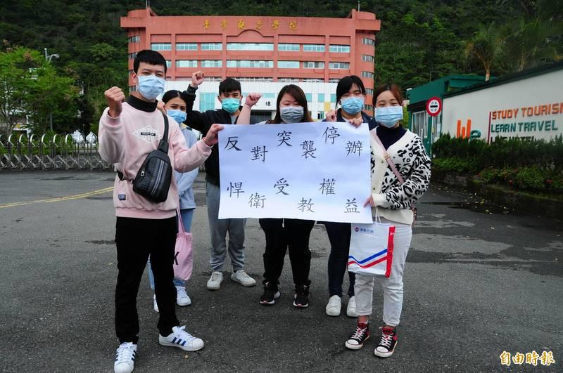 台灣觀光學院學生在教育部、學校召開說明會之前,在校門口舉大字報抗議,希望能讓學生留在原校畢業。(記者花孟璟攝)