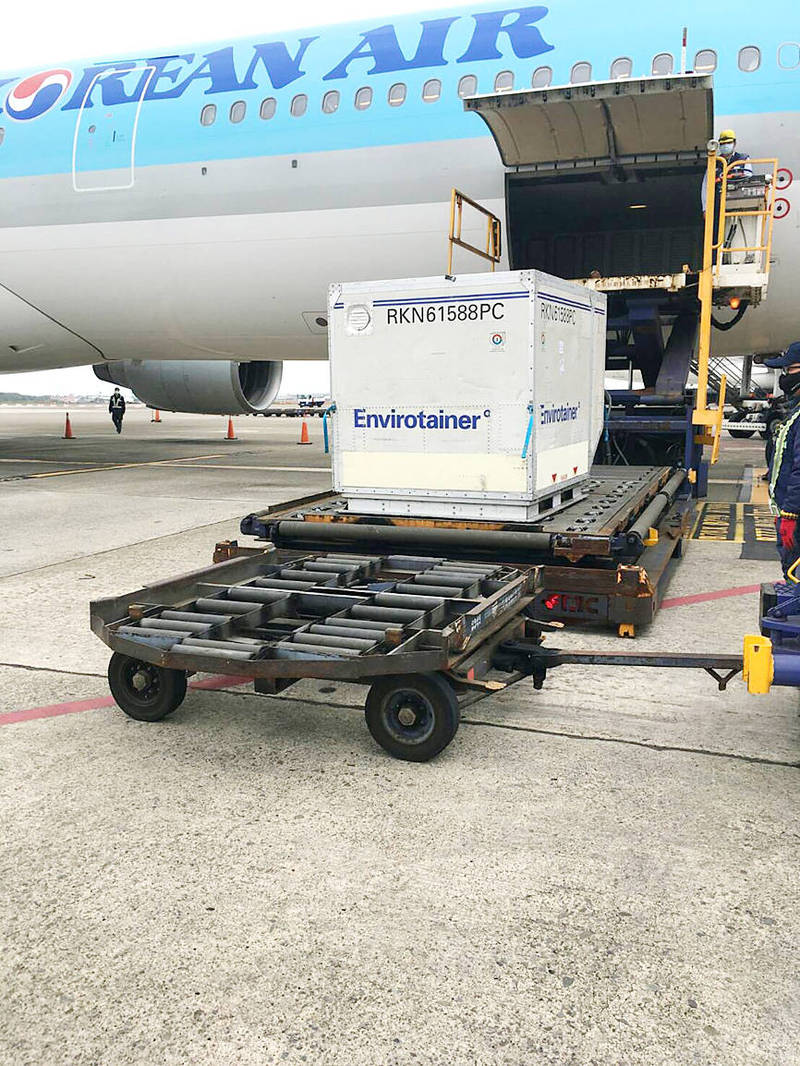 The first batch of COVID-19 vaccines to arrive in Taiwan — 117,000 doses of the AstraZeneca drug — are unloaded from a Korean Air plane at Taiwan Taoyuan International Airport yesterday. Photo: CNA