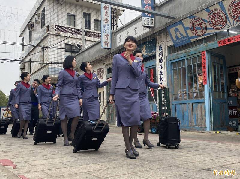 華信空姐空少穿著制服、拉行李箱在陽翟老街神氣掃街。(記者吳正庭攝)