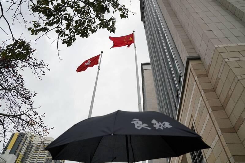 1日在西九龍法院外聲援出庭的民主派人士,撐起寫有「良知」的黑傘,背景上方為中國五星旗和香港特區旗。(路透)