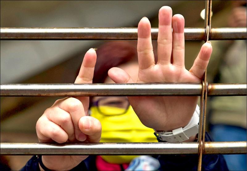 香港民主派支持者四日在香港法院外,隔著柵欄比出象徵反送中示威口號「五大訴求、缺一不可」的手勢。(美聯社)