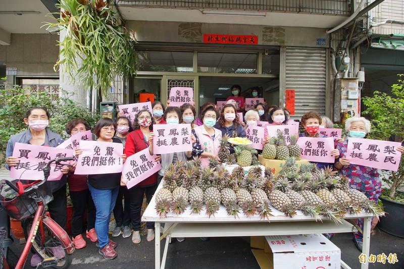 議員邱素貞(中)自掏腰包買了上百顆台灣鳳梨,分送水噹噹關懷據點長輩與志工。(記者何宗翰攝)