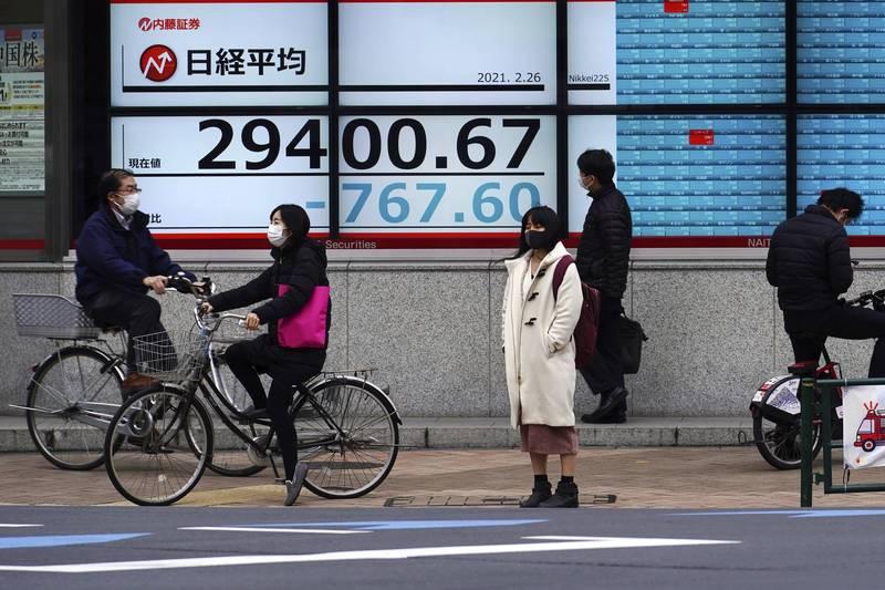 2月26日東京街頭的男、女路人。(美聯社)