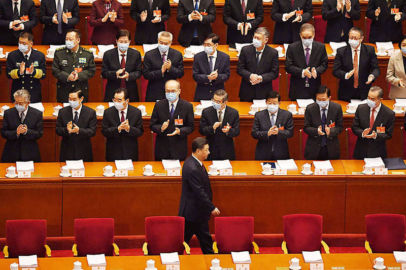 Delegates applaud as Chinese President Xi Jinping, center, arrives for the opening ceremony of the Chinese National People's Congress at the Great Hall of the People in Beijing yesterday. Photo: AFP