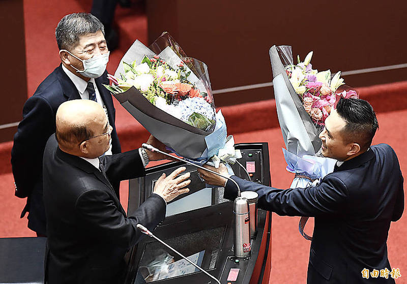 Chinese Nationalist Party (KMT) Legislator Charles Chen, right, gives bouquets of flowers to Premier Su Tseng-chang, front left, and Minister of Health and Welfare Chen Shih-chung during a legislative session in Taipei yesterday to thank them for their COVID-19 pandemic prevention efforts. Photo: Chien Jung-fong, Taipei Times