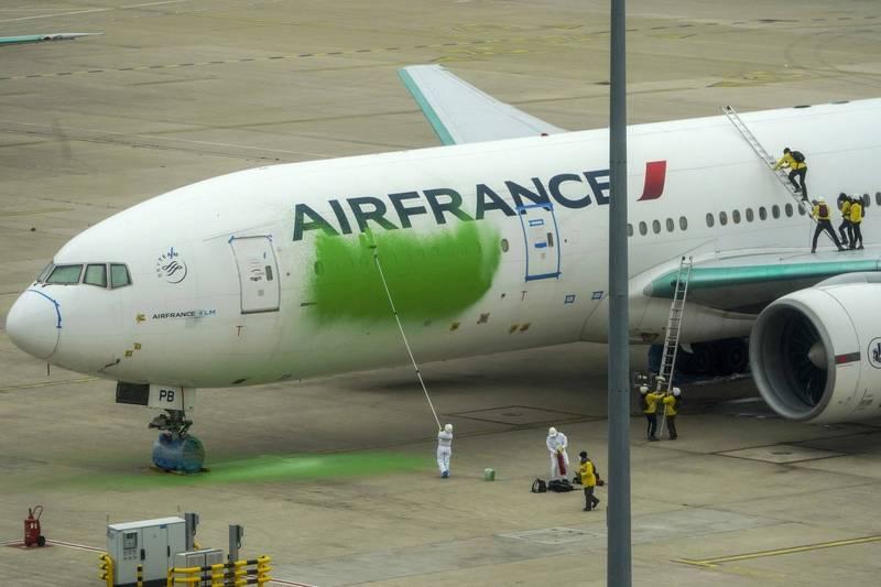 綠色和平組織於法國戴高樂國際機場將一架客機進行噴漆,表達對法國政府氣候變遷政策的不滿,圖為機場工作人員正在清洗客機。(美聯社)