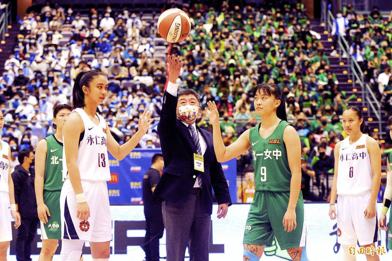 Minister of Health and Welfare Chen Shih-chung performs the tip-off of a High School Basketball League game between Tainan Municipal Yongren High School and Taipei First Girls' High School yesterday at the Taipei Arena. Thanks to Taiwan's ongoing success in combating the COVID-19 pandemic, Chen and other fans were able to watch the game in person at the arena. Photo: Lin Cheng-kung, Taipei Times