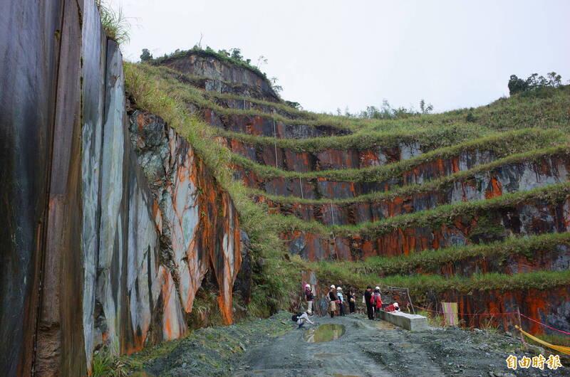 巨人的樓梯!花蓮萬榮鄉瑞欣石礦目前仍開採中,首度開放舉辦藝術展,礦場墨綠色的蛇紋石夾雜白色石英成份,被金剛鎖鋸、鍊鋸平整切割,每一階高度達1樓半、約6米至9米高度,形成超過10個巨大階梯,裸露的石壁氧化後變紅,視覺十分震撼。(記者花孟璟攝)