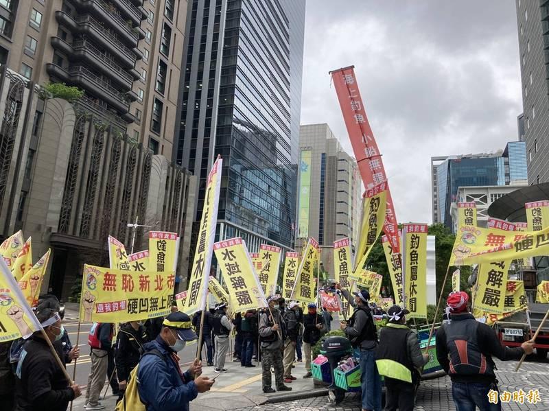 釣魚團體手持標語到市府前抗議。(記者邱書昱攝)